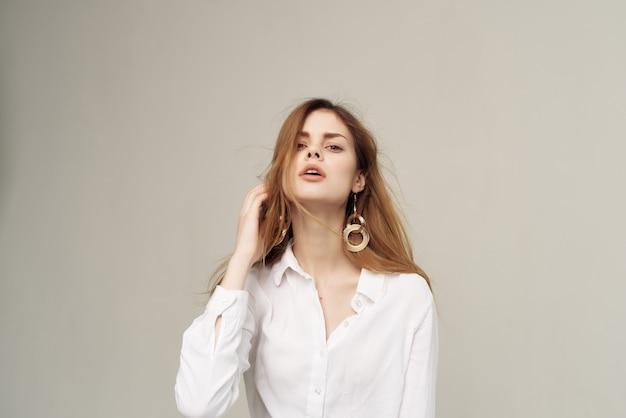 Jolie femme avec une chemise blanche glamour de décoration de cheveux rouges