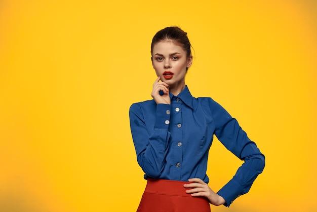 Jolie femme en chemise bleue gesticulant avec ses mains et jupe rouge jaune