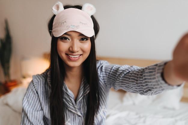 Jolie femme en chemise rayée et masque de sommeil sourit et prend selfie