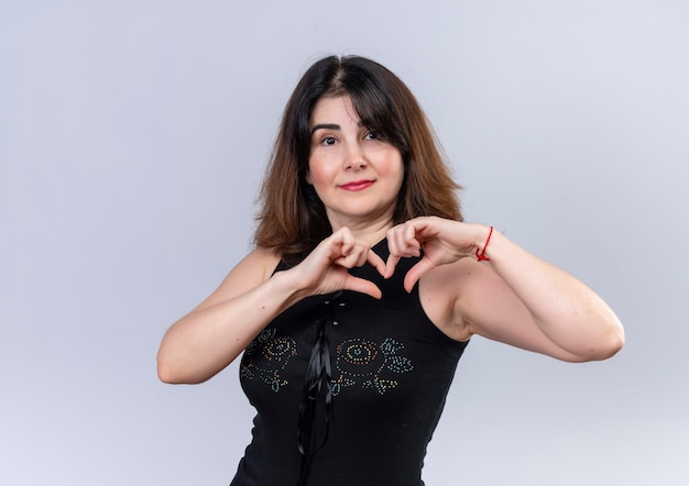 Jolie femme en chemisier noir montrant son amour avec les doigts