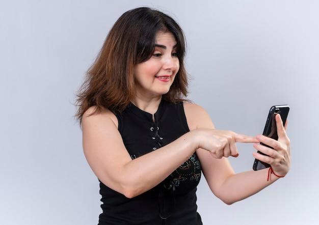 Jolie femme en chemisier noir pointant joyeusement sur le téléphone