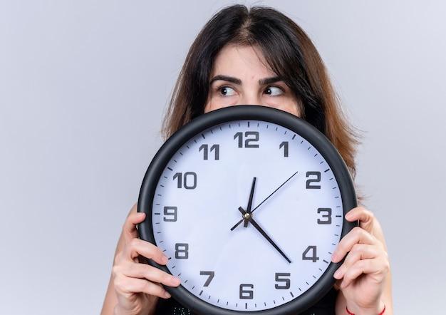 Jolie femme en chemisier noir se cachant derrière l'horloge à la recherche en plus