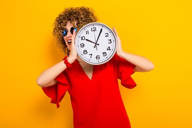 Jolie femme avec des cheveux courts et bouclés avec des horloges