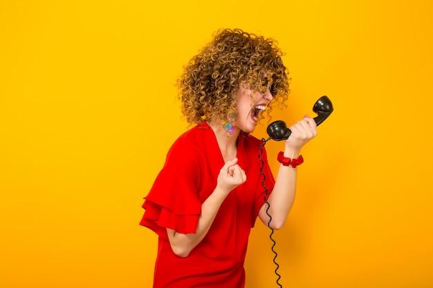 Jolie femme avec des cheveux courts et bouclés avec téléphone
