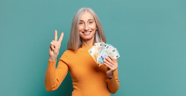 Jolie femme cheveux gris avec des billets