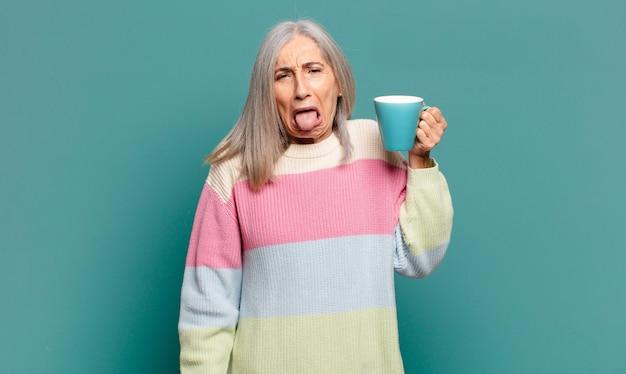 Jolie femme cheveux gris avec un café ou un thé