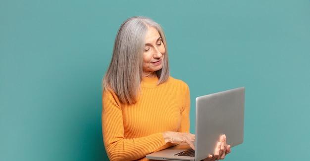 Jolie femme cheveux gris avec un ordinateur portable.