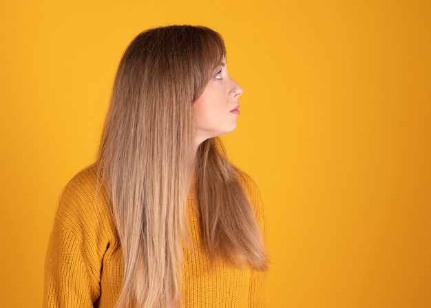 Jolie femme, cheveux raides blonds, regardant sur le côté, mur jaune