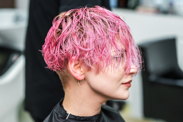 Jolie femme avec des cheveux roses courts humides glamour au salon de beauté.