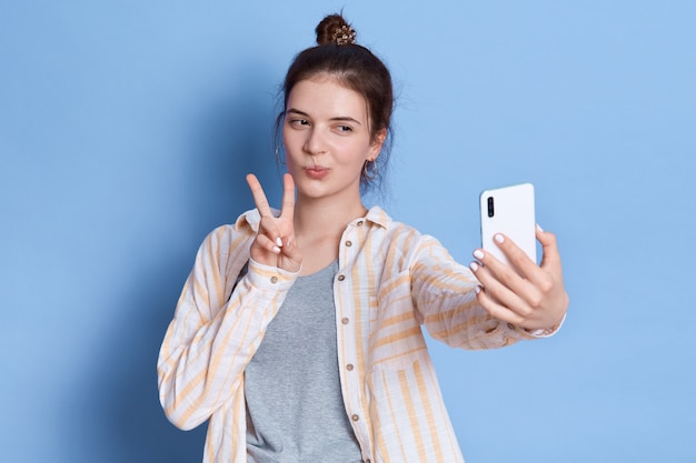 Jolie femme avec chignon en tenue décontractée montrant le geste de victoire ou de paix tout en prenant selfie et gesticulant signe v, fille brune.