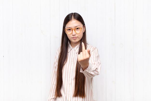 Jolie femme chinoise contre un mur blanc