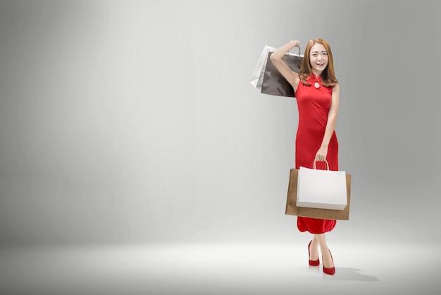 Jolie femme chinoise avec une robe cheongsam portant des sacs