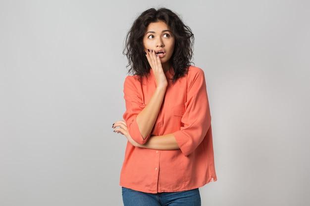 Jolie femme choquée à côté, visage surpris, émotion drôle, latin, chemisier orange, élégant, isolé, jeune et naturel