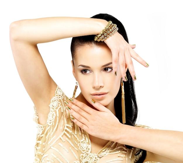 Jolie femme avec des clous dorés et de beaux bijoux en or isolé sur fond blanc