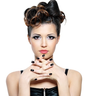 Jolie femme avec une coiffure élégante et des ongles noirs. maquillage des yeux mode