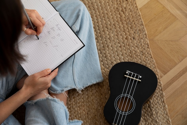 Jolie femme composant une nouvelle chanson sur ukulélé