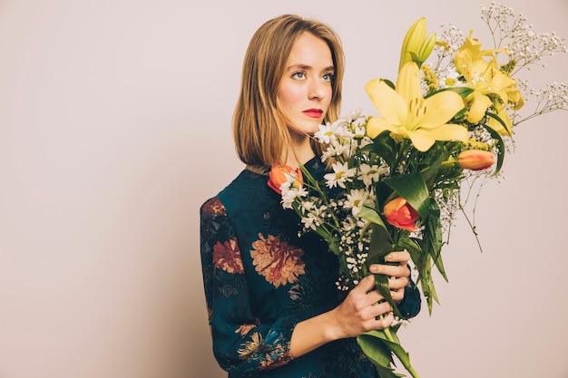 Jolie femme confiante avec gros bouquet de fleurs