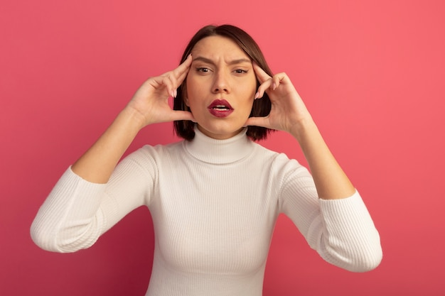 Jolie femme confiante met les doigts sur les tempes isolées sur le mur rose
