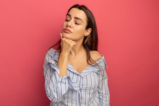 Jolie femme confiante met la main sur le menton et regarde côté isolé sur mur rose