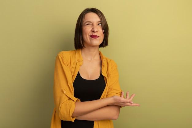 Jolie femme confuse clignote des yeux et regarde à côté isolé sur mur vert olive