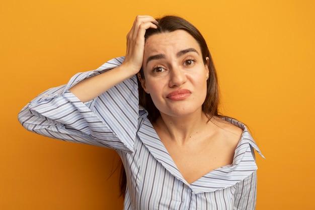 Jolie femme confuse met la main sur la tête isolée sur un mur orange