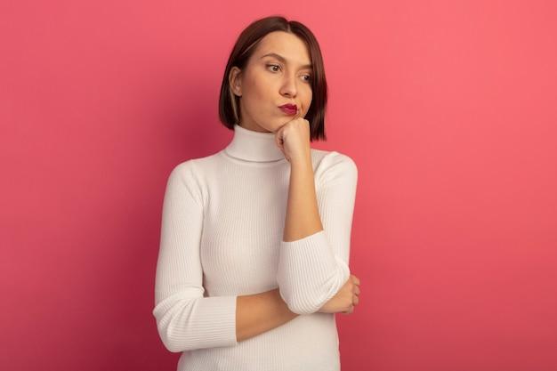 Jolie femme confuse met le poing sur le menton et regarde le côté isolé sur le mur rose
