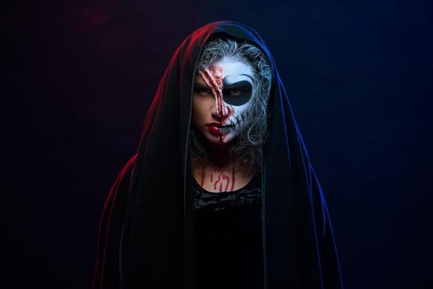 Jolie femme en costume d'halloween avec maquillage squelette