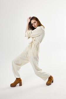 Jolie femme en costume marron chaussures posant fond clair. photo de haute qualité