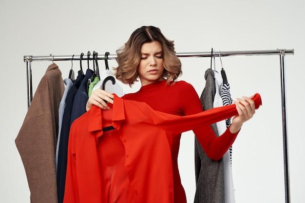 Jolie femme à côté de vêtements mode émotions de vente au détail amusantes. photo de haute qualité