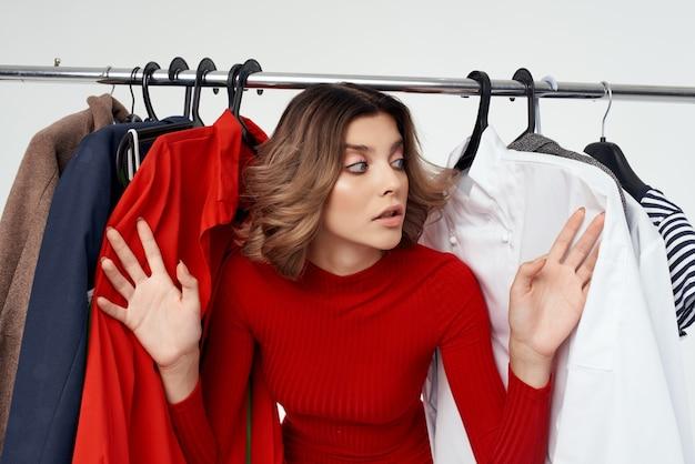 Jolie femme à côté de vêtements mode fun fond clair au détail