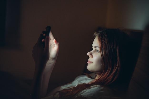 Jolie femme couchée dans son lit avec le téléphone à la main au repos nocturne avant le coucher.