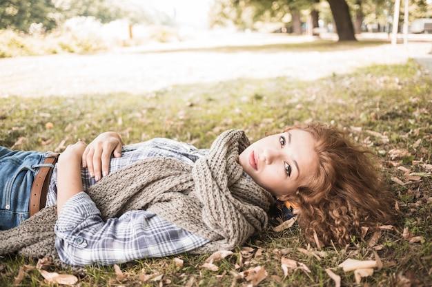 Jolie femme couchée sur l'herbe dans le parc