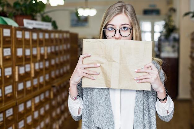 Jolie femme couvrant la bouche avec un livre