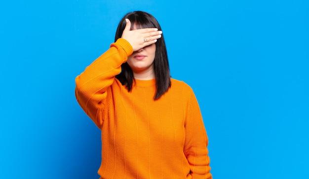Jolie femme couvrant les yeux d'une main se sentant effrayée ou anxieuse, se demandant ou attendant aveuglément une surprise