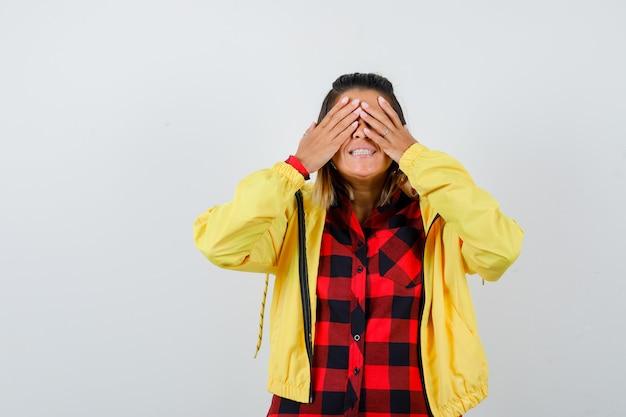 Jolie femme couvrant les yeux avec les mains en chemise, veste et semblant excitée. vue de face.
