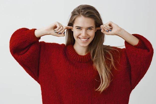 Jolie femme créative prête à nous épater. heureuse incroyable femme européenne, couvrant les oreilles avec les index et souriant avec une expression intrigante, ayant une idée en tête sur le mur gris