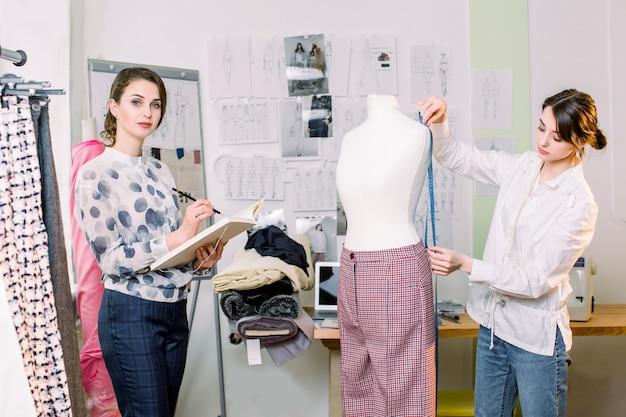 Jolie femme créatrice de mode tient un crayon et des feuilles de papier, travaillant avec une nouvelle collection de pantalons, regardant la caméra. tailleur femme prenant des mesures de mannequin avec ruban à mesurer