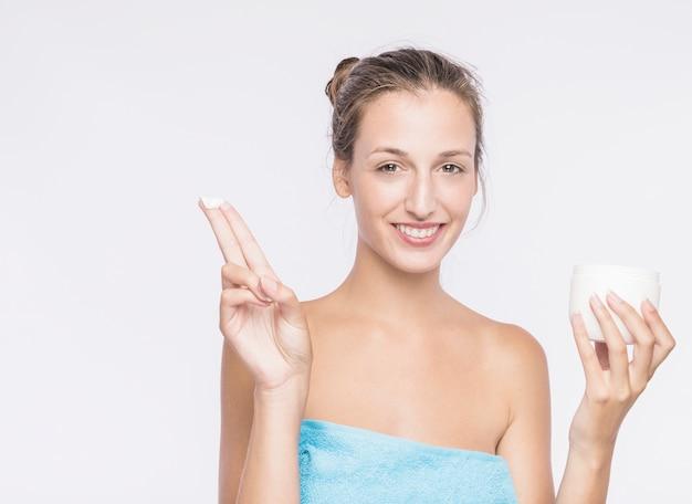 Jolie femme avec une crème pour le corps dans une serviette