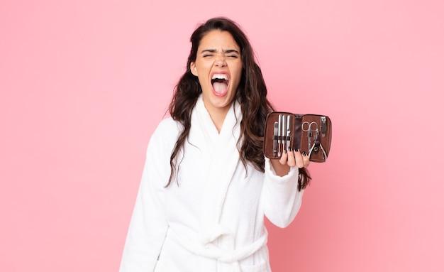 Jolie femme criant agressivement, l'air très en colère et tenant un sac de maquillage avec des outils à ongles