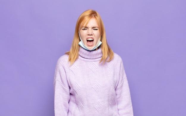 Jolie femme criant de manière agressive, à la très en colère, frustré, indigné ou agacé, crier non