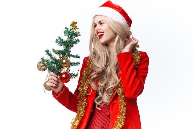 Jolie femme dans l'arbre de noël de costume de père noël avec la mode de décoration de jouets