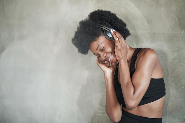 Jolie femme dans les écouteurs. portrait de jeune fille afro-américaine dans des vêtements de fitness ayant une pause après l'entraînement