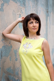 Jolie femme dans l'été de la ville posant près d'un vieux mur coloré