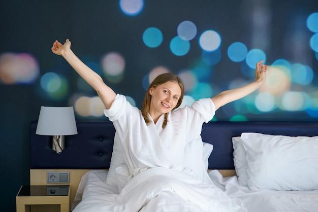 Jolie femme dans un manteau blanc au lit avec les mains vers le haut