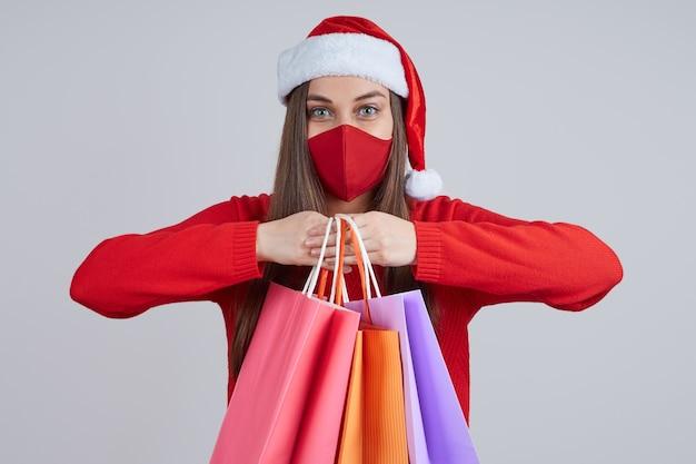 Une jolie femme dans un masque de protection, portant un bonnet de noel, détient plusieurs sacs en papier