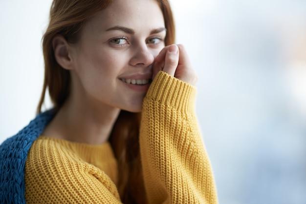 Jolie femme dans un pull jaune se cachant derrière une couverture près de l'intérieur de la maison confort fenêtre
