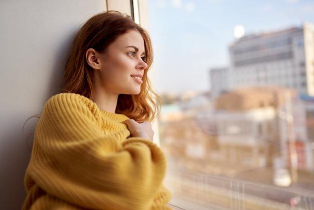 Une jolie femme dans un pull jaune se trouve sur le rebord de la fenêtre et regarde par la fenêtre