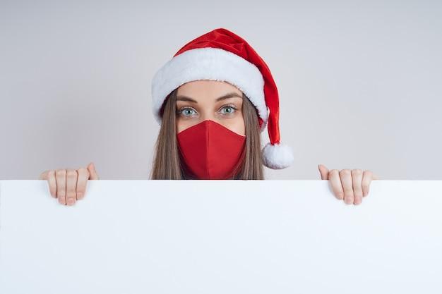 Jolie femme dans un pull rouge, dans un masque de protection, dans un bonnet de noel