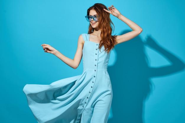 Jolie femme dans une robe bleue fond bleu mode de vie. photo de haute qualité