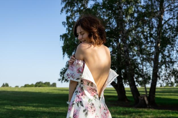 Jolie femme dans une robe légère avec des épaules nues et un imprimé floral se tient avec son dos
